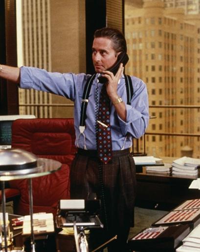 """Gordon Gekko. Všichni si pamatují jeho výrok o tom, že """"Chamtivost je dobrá,"""" ale v paměti nám utkvěl také Gordonův cit pro detail (a jeho povrchnost). Kšandy, košile s kontrastním límcem, a sofistikované spony na kravatu neevokovaly pouze moc, přinášely také pocit nadřazenosti."""