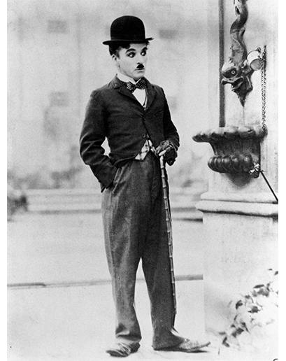Charlie Chaplin, první filmová hvězda, nosil přehnaně zvýrazněnou verzi každodenního dobového obleku – upnuté sportovní sako a balónové kalhoty.