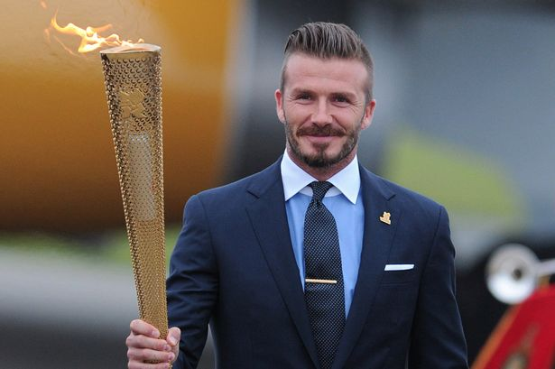 Former England footballer David Beckham carries the Olympic torch as it arrives at RNAS Culdrose air base in Cornwall, south-west England