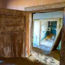 Kolmanskop – německé město duchů uprostřed namibijské pouště - Kolmanskop-through-the-door-frames